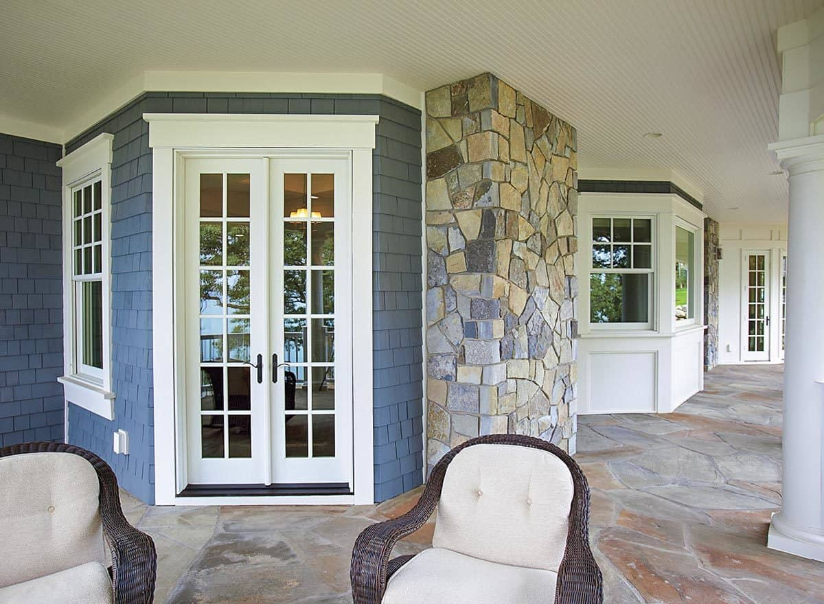A closeup look at the covered porch that's accessible through the french door offering wicker seats over stone flooring.