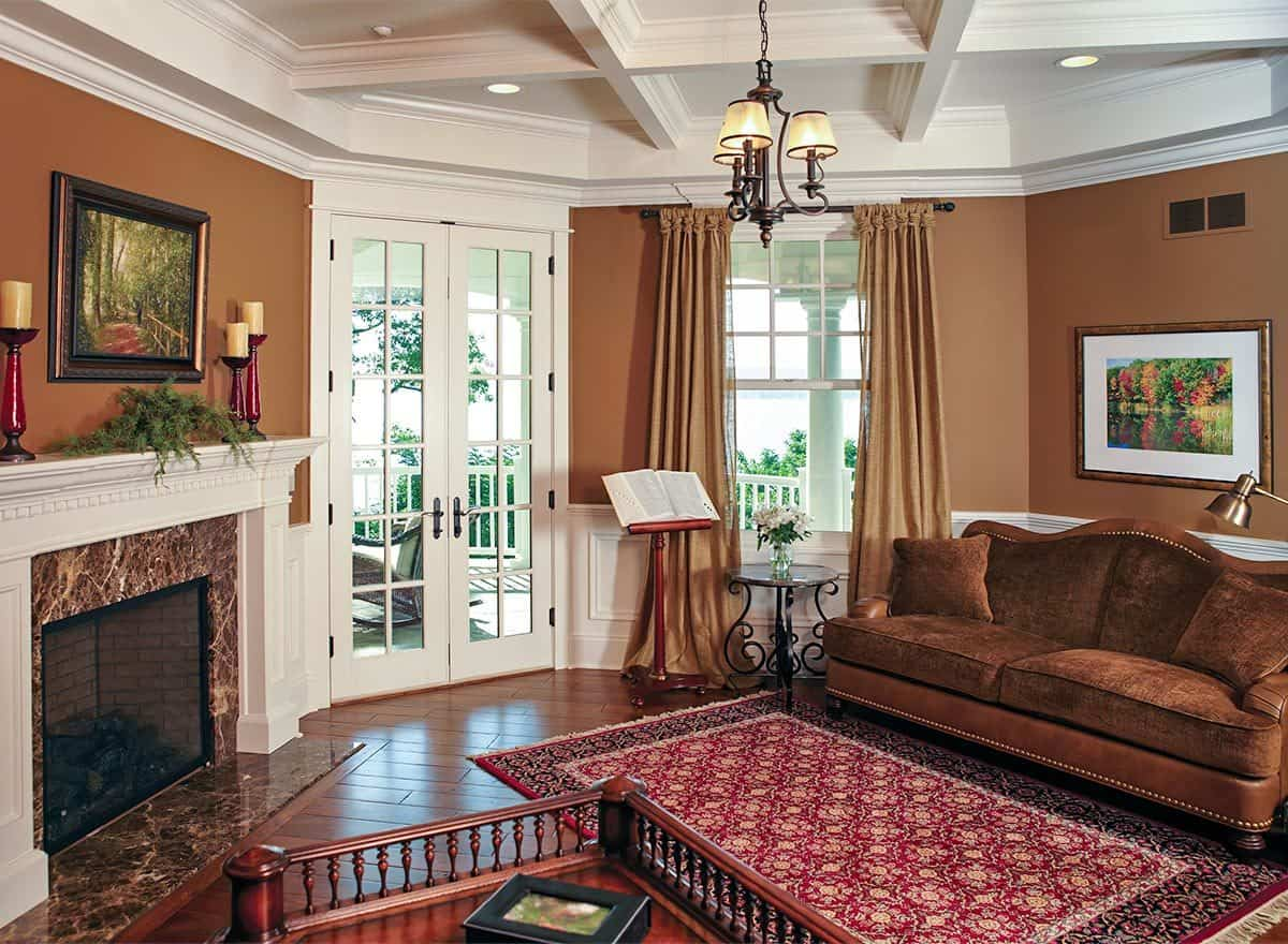 Sitting room with a corner fireplace, a coffered ceiling and french door that opens out to the covered porch.