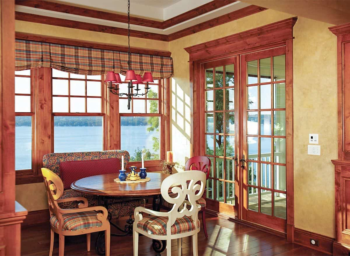Breakfast nook with a round dining table surrounded by a floral bench and cushioned chairs that match the checkered roman shades.