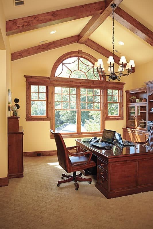Home office with beige carpet flooring and cathedral beamed ceiling mounted with wrought iron chandelier.