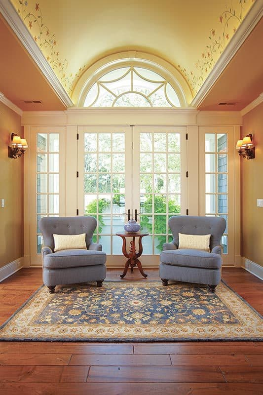 The vestibule showcases a stunning barrel vaulted ceiling and wide plank flooring topped by a floral rug.