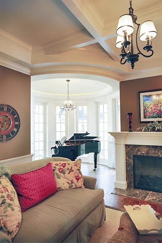 Living room with white coffered ceiling and a circular space filled with a baby grand piano.
