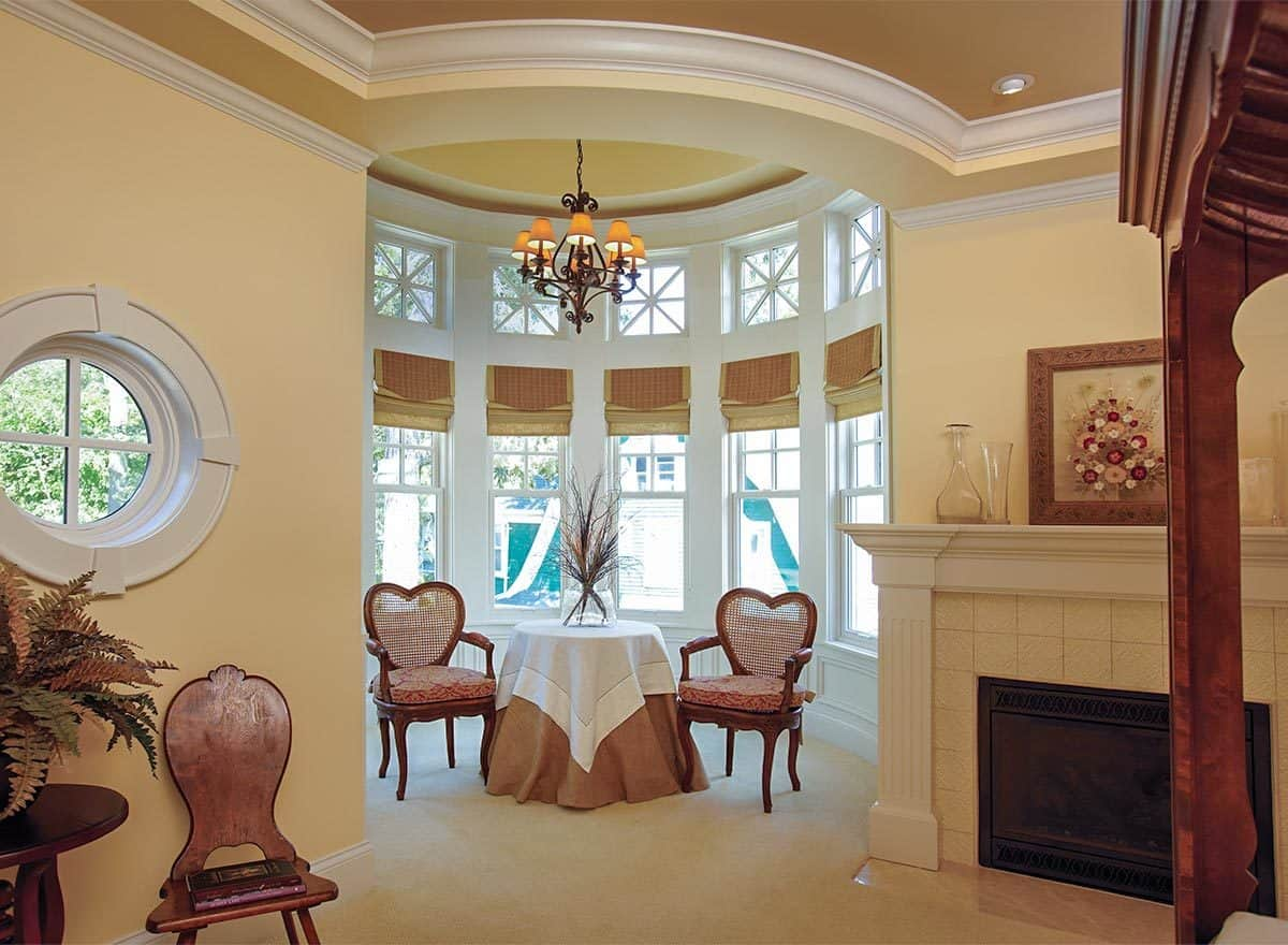 Circular sitting area offers cushioned seats and a round skirted table under the ornate chandelier.