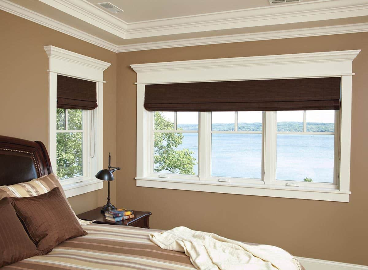 Bedroom with brown walls and white framed windows overlooking the outdoor scenery.