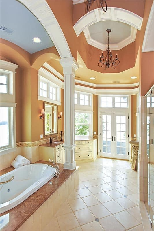 The master bathroom is equipped with white vanities, a deep soaking alcove tub, and a separate shower.