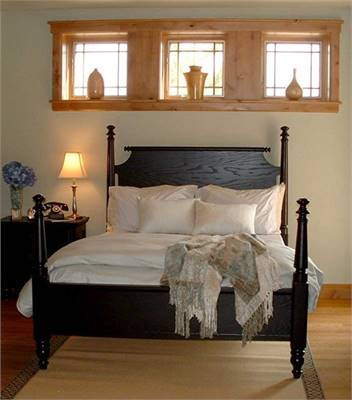 The bedroom offers a dark wood nightstand and a four-poster bed situated under the wooden framed windows.