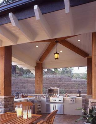Outdoor kitchen equipped with stainless steel appliances and a wooden dining set matching with the columns and trims.