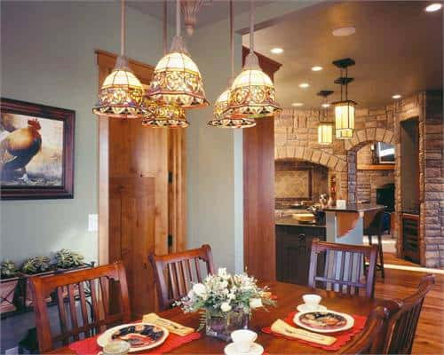 Dining room filled with gorgeous glass dome pendants and a wooden dining set that blends in with the rich hardwood flooring.