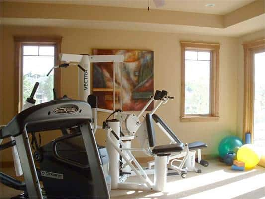 Exercise room with beige walls, tray ceiling, and wooden framed windows that allow natural light in.
