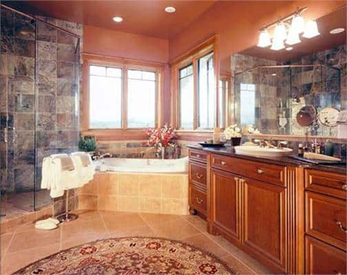 The primary bathroom is equipped with a walk-in shower, deep soaking tub, and a wooden vanity topped with a vessel sink.