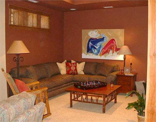 The media room is filled with L-shaped sectional, wooden furniture, and an interesting painting fixed against the brown wall.