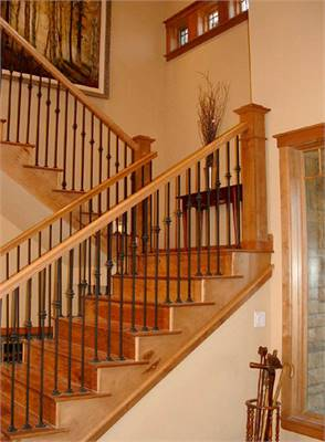 Wooden staircase with wrought iron spindles leading to the bedrooms.