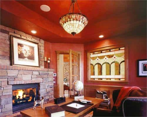 Home office with a brick fireplace, red walls and a beautiful glass dome pendant hanging from the tray ceiling.