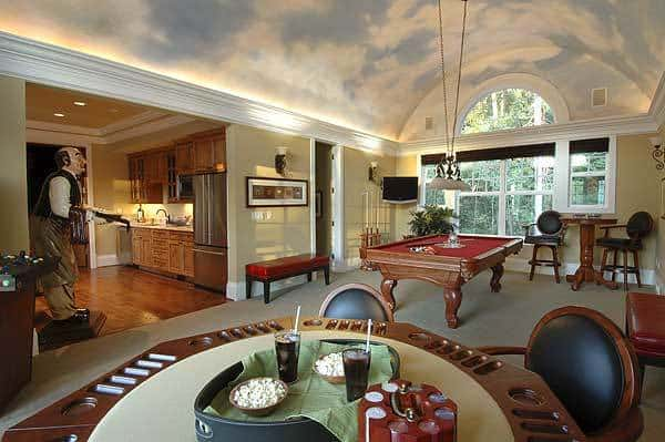 Luxury game room with barrel ceiling. large windows, a billiard table, card table, and kitchenette.