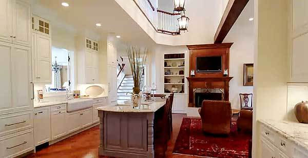 The gorgeous kitchen with farmhouse sink and a central kitchen island is just near the family room.