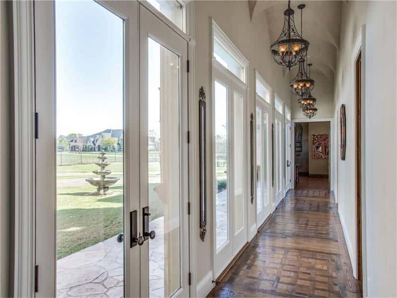Hallway with french doors and vaulted ceiling mounted with wrought iron pendants.