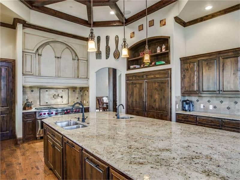 The kitchen offers natural wood cabinetry, a cooking alcove, and a massive granite top island fitted with undermount sinks.