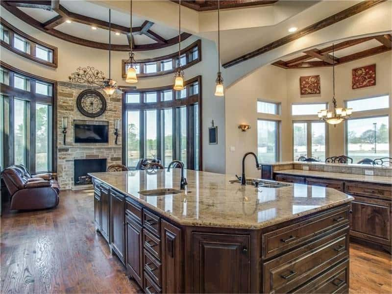 Across the kitchen is the keeping room with a warm fireplace and glass-paneled windows.