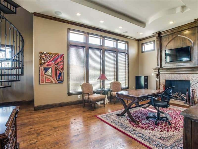 The home office is filled with a fireplace, cushioned armchairs, and a wooden desk sitting over a classic area rug.