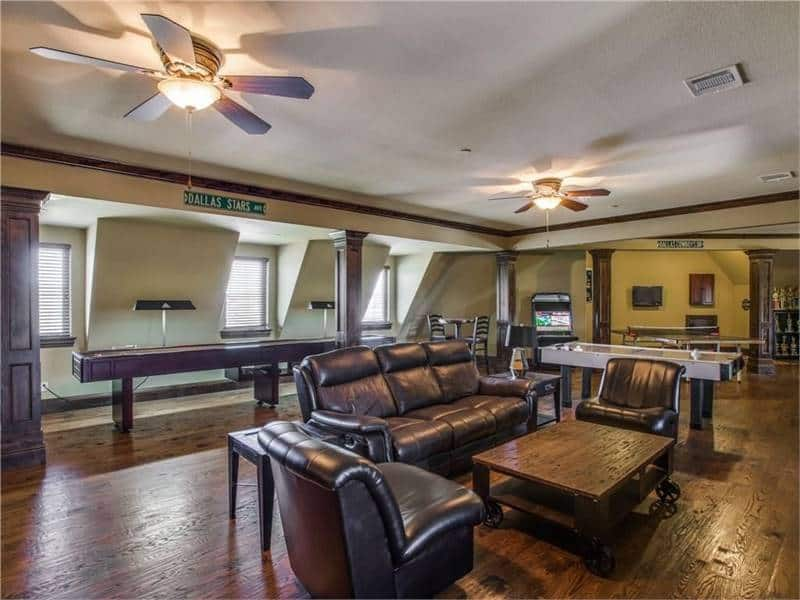 Game room with black leather seats and a wooden coffee table that blends in with the hardwood flooring.