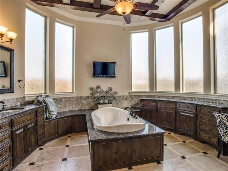 The primary bathroom is equipped with wooden vanities and a deep soaking tub under the beamed ceiling.