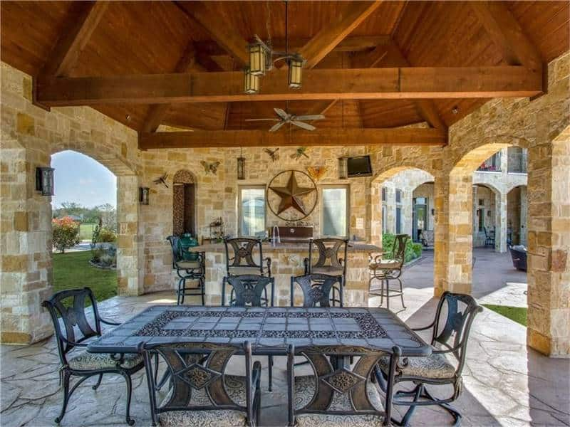 Outdoor living with a bar and metal dining set surrounded by open archways.