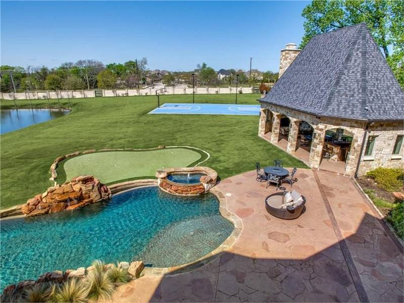 Aerial view of the outdoor space showing the gazebo, stunning pool with spa, mini-golf course, and a basketball court.