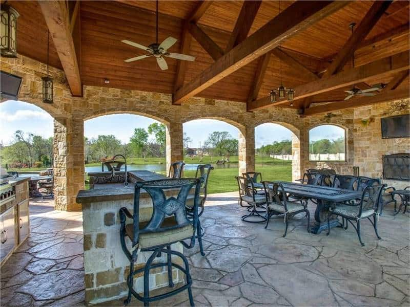 The outdoor living has a flagstone flooring and a vaulted beamed ceiling with hanging fans and pendant lights.