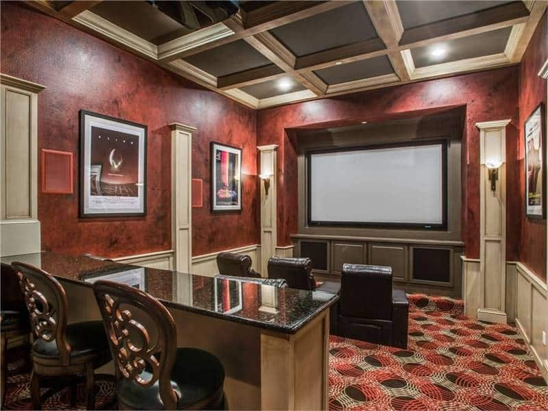 Home theater with coffered ceiling and red walls adorned by posters, columns and cream wainscoting.