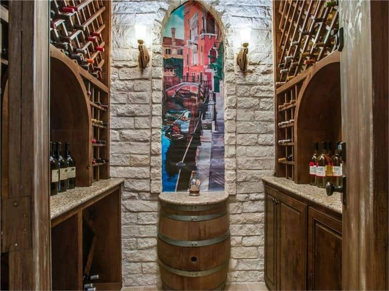 Wine cellar with crisscross shelves and a barrel counter under the arched inset wall.