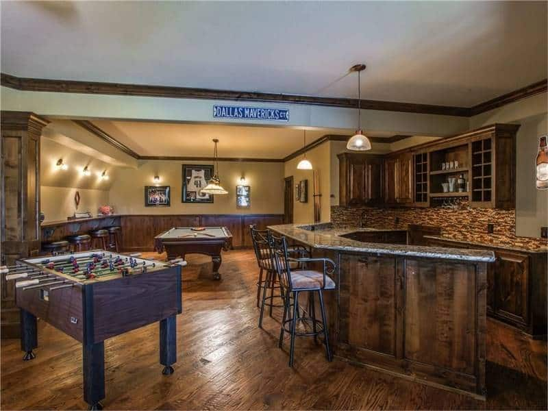 Game room with various tables and a wet bar with two-tier counter and ornate metal chairs.