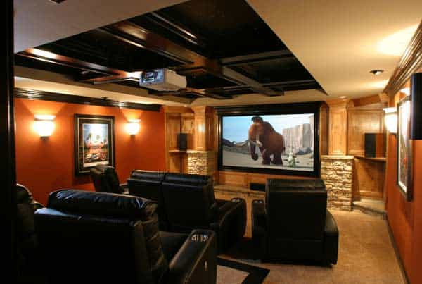 Media room with black recliners and framed posters flanked by warm sconces.