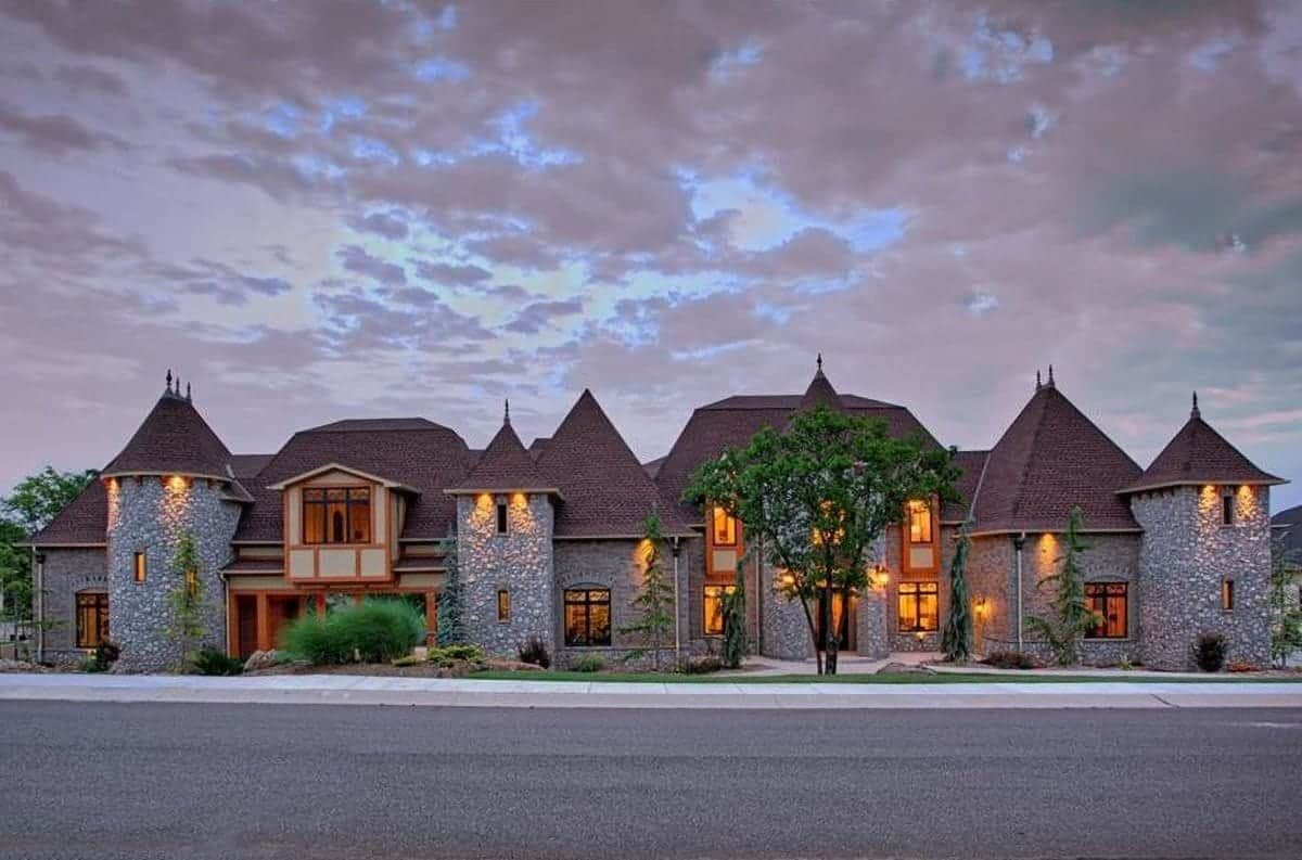 Home's facade with steeply pitched roofs and stone cladding complemented with warm, ambient lights.