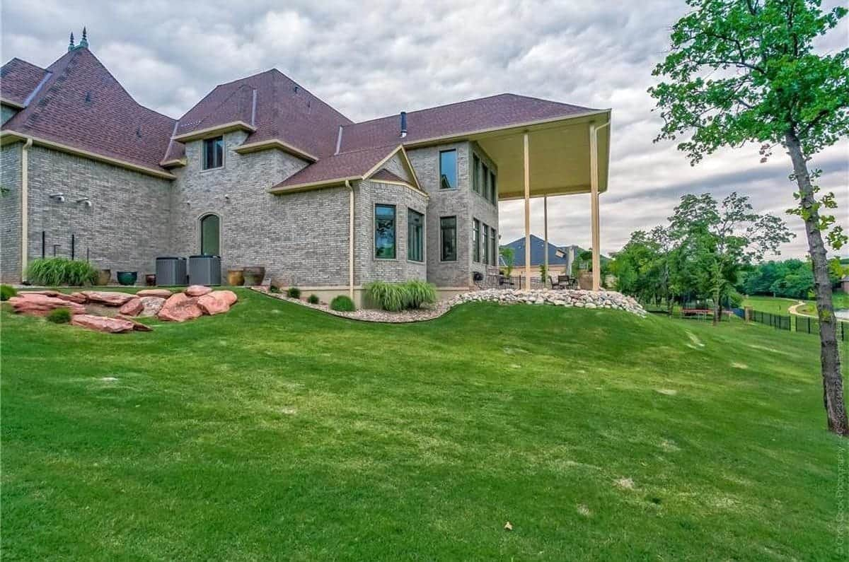Home's angled side view shows the patio supported by tall rustic columns overlooking the serene surrounding.