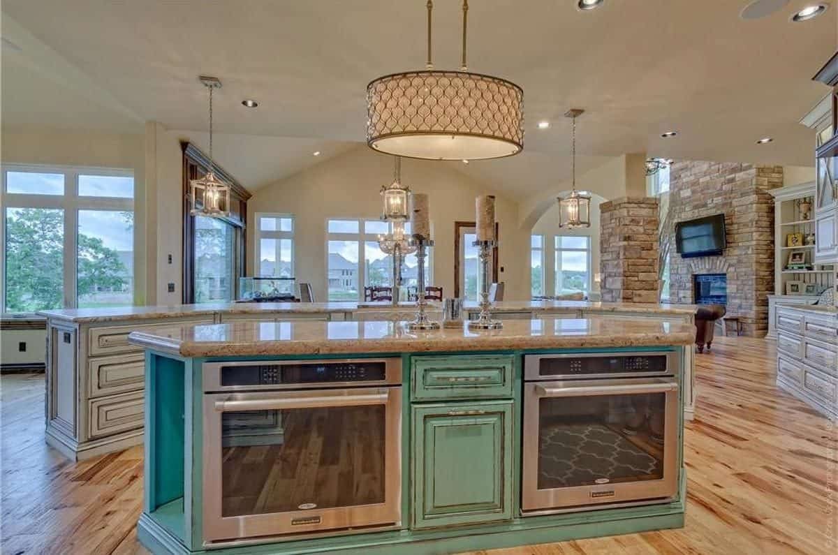 A stylish drum chandelier hanging over the center island illuminates the kitchen along with warm pendants and recessed ceiling lights.