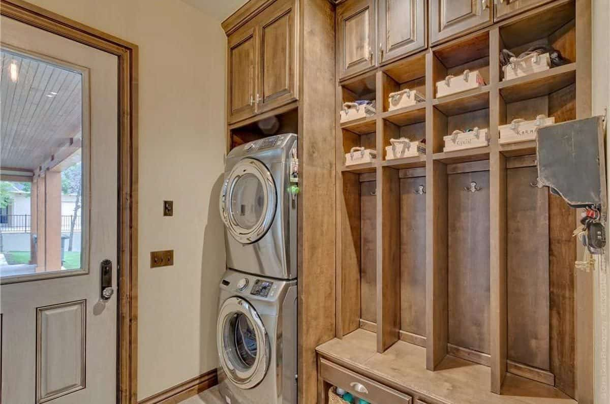The laundry room has a front load washing machine and dryer along with wooden cabinets and shelves filled with storage baskets.