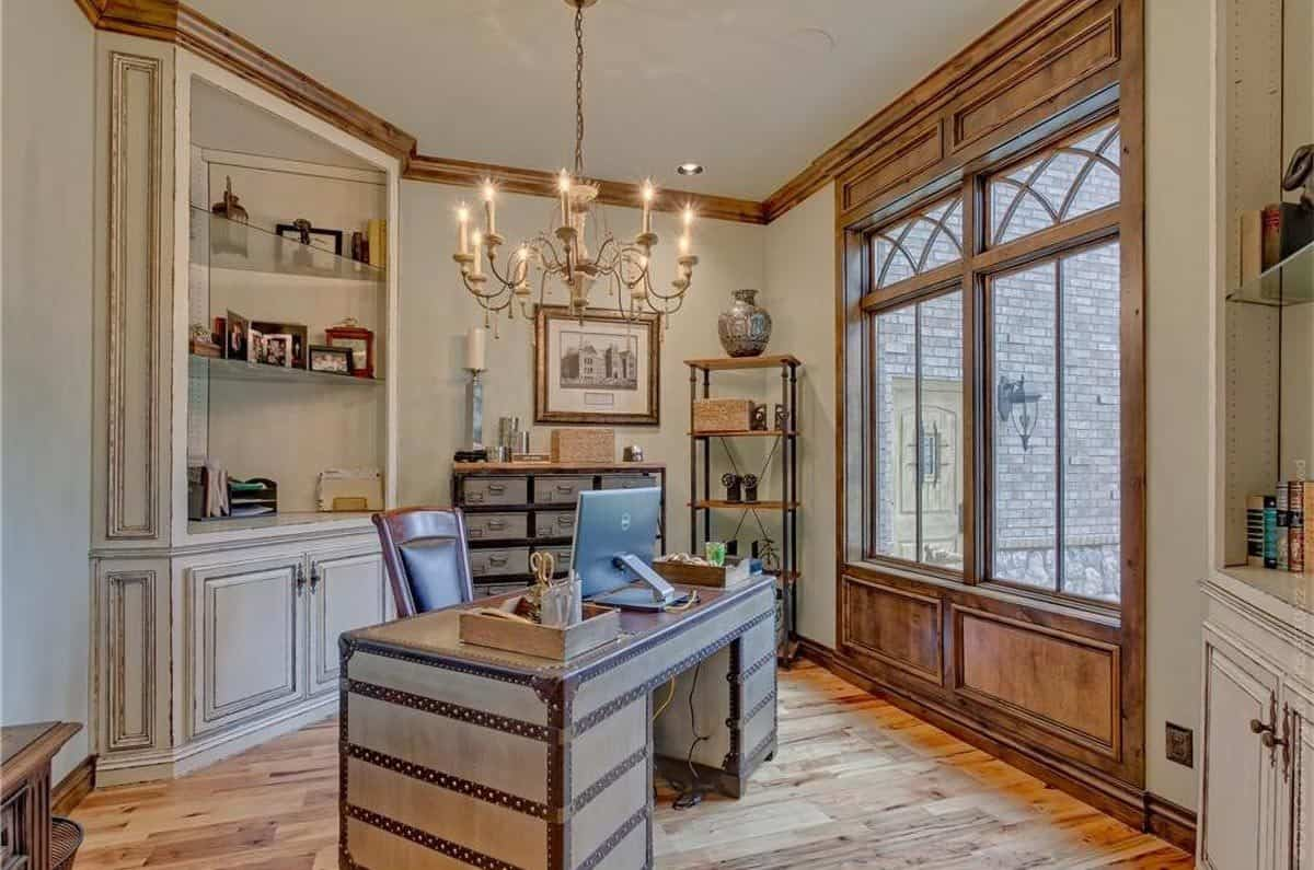 The home office features a warm candle chandelier. and a stylish wooden desk paired with a leather chair.