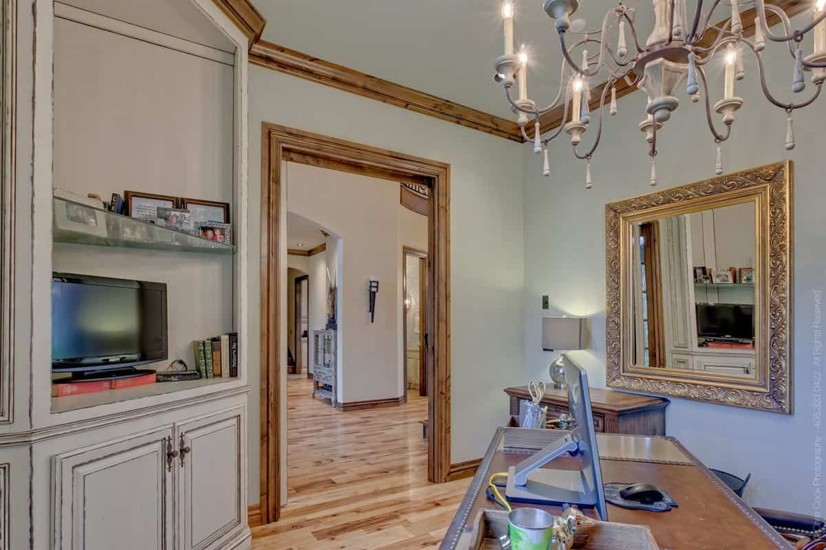 The opposite side view shows the TV and a classy gilded mirror adorning the beige walls.