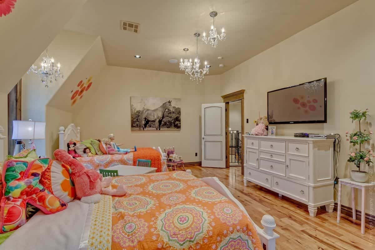 Kids' bedroom with crystal chandeliers. a wall-mounted TV above the white dresser, and two matching beds flanking the desk with green chairs.