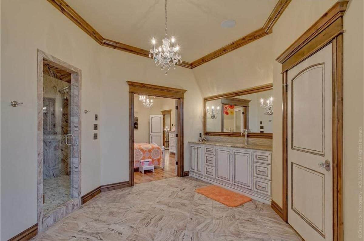 The other view of the bathroom shows another sink vanity and crystal chandelier hanging from the beige ceiling surrounded by wooden crown molding.