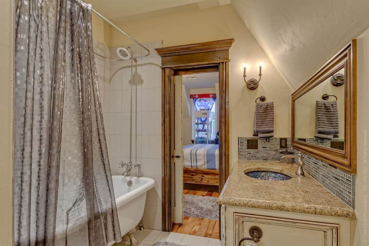 The boy's bathroom offers a tub and shower combo and a sink vanity paired with a rectangular mirror.