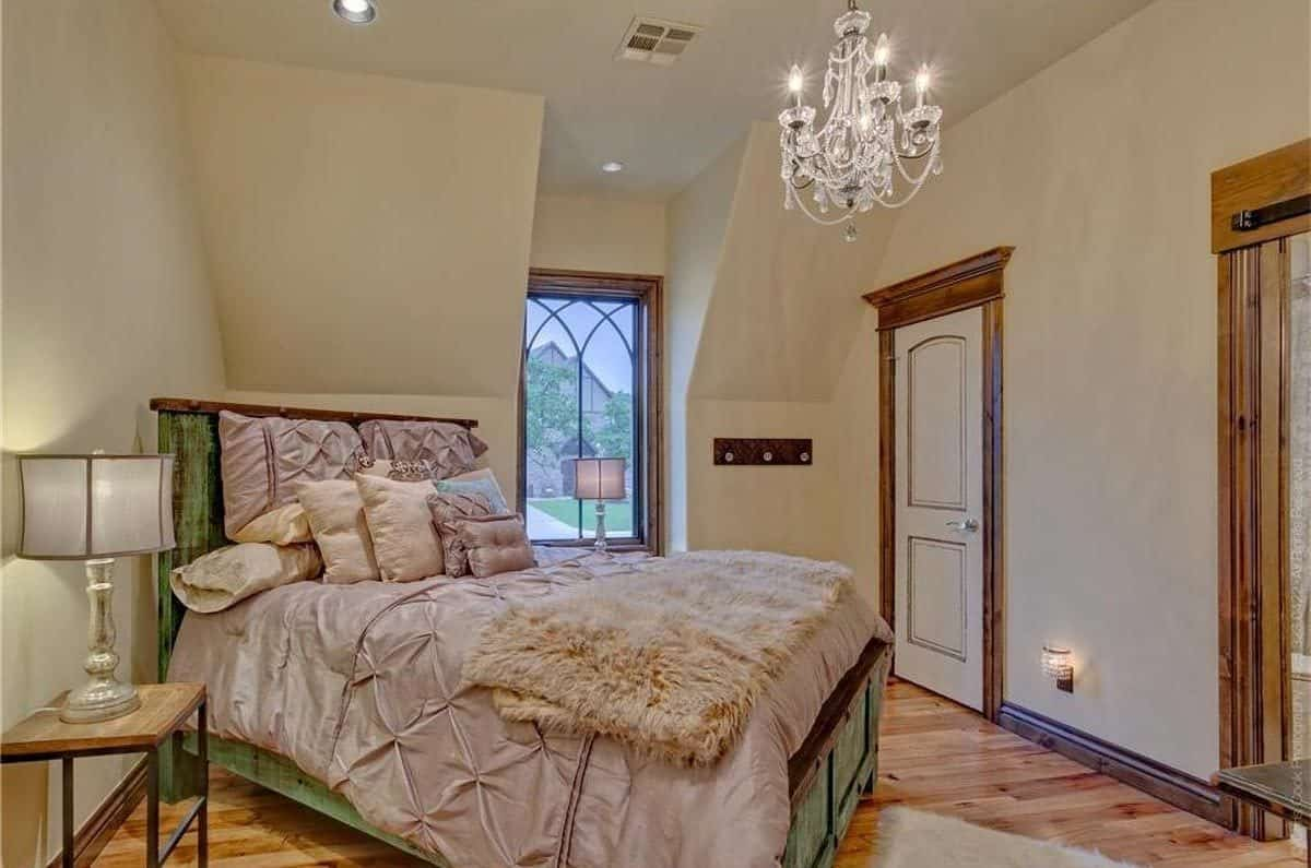 This bedroom has a glass beaded chandelier and a distressed green bed complemented with wooden nightstands and drum table lamps.