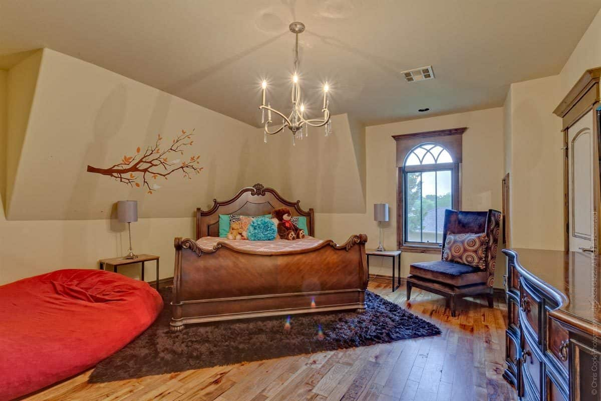 This bedroom has a candle chandelier, a velvet wingback bed, and a cozy wooden bed over a gray area rug.