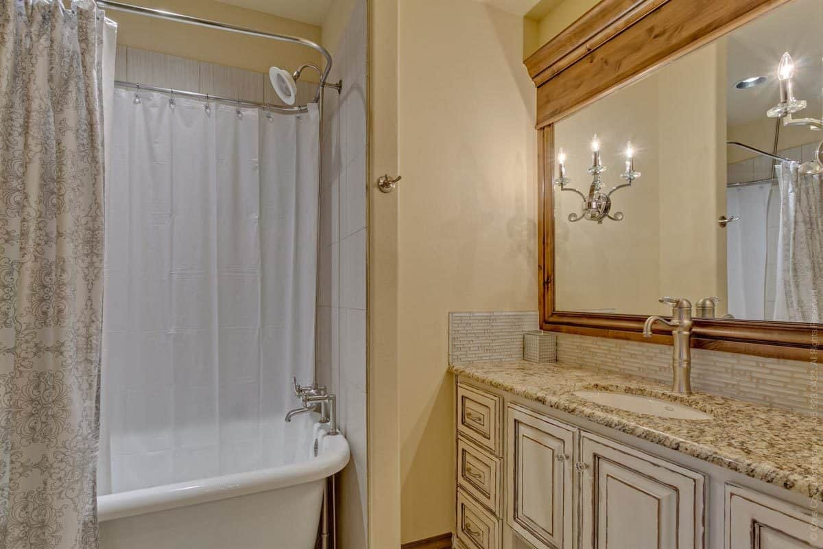 Bathroom with a granite top sink vanity and a tub and shower combo enclosed in a classy patterned curtain.
