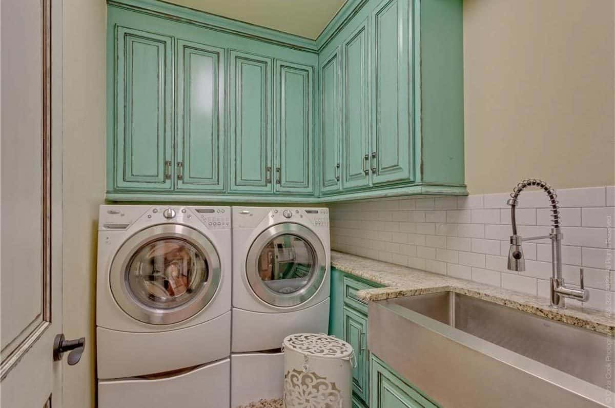 The laundry room is filled with green cabinets. white appliances, and a chrome trough sink paired with a pull-down sprayer.