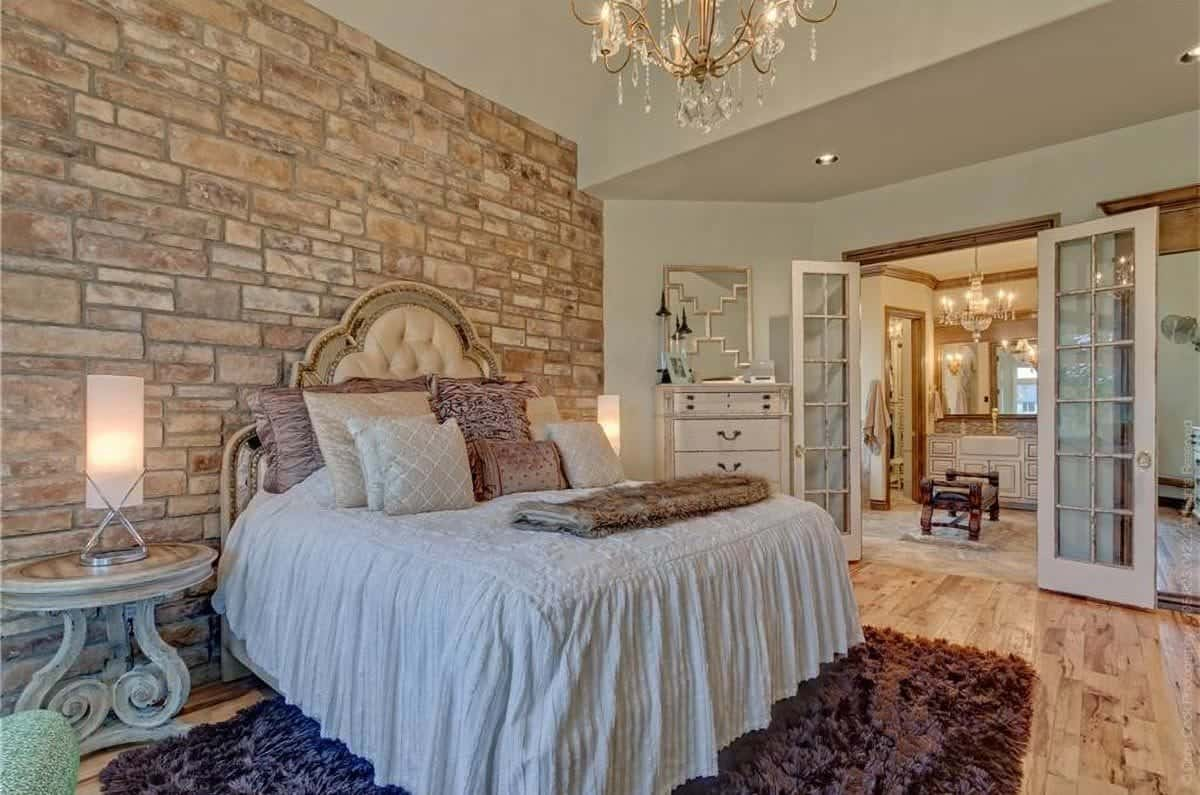 The opposite view shows the brick accent wall and a french door that opens out to the primary bathroom.