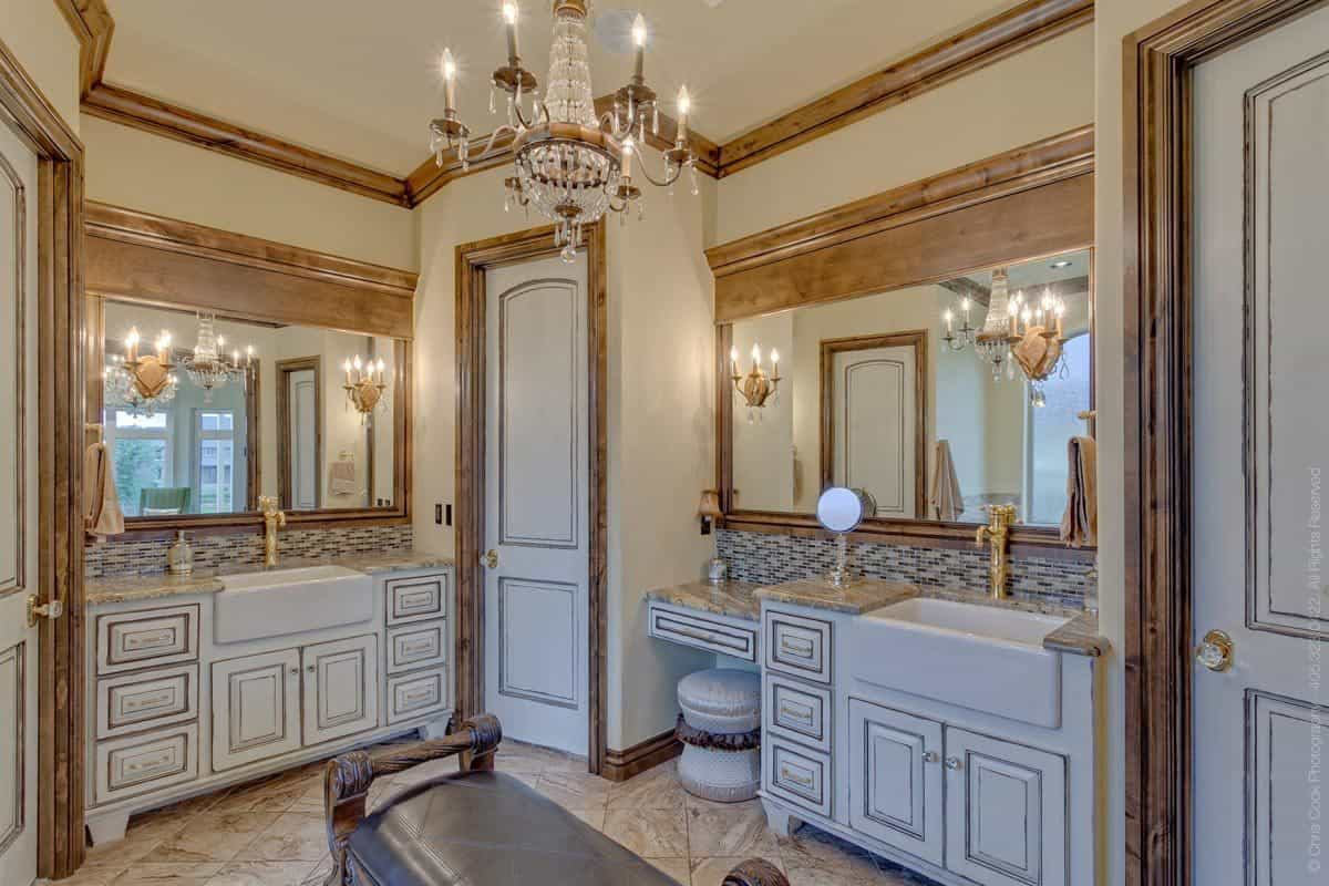 There's also a water closet flanked by white vanities with farmhouse sinks and wooden framed mirrors.