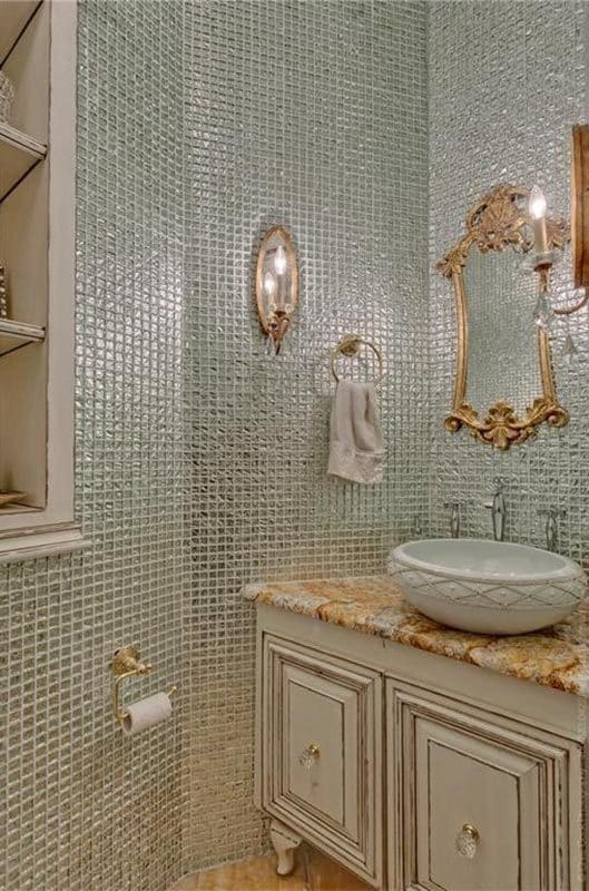 Powder room with a vessel sink vanity, and green-tiled walls mounted with warm sconces and an ornate gold mirror.