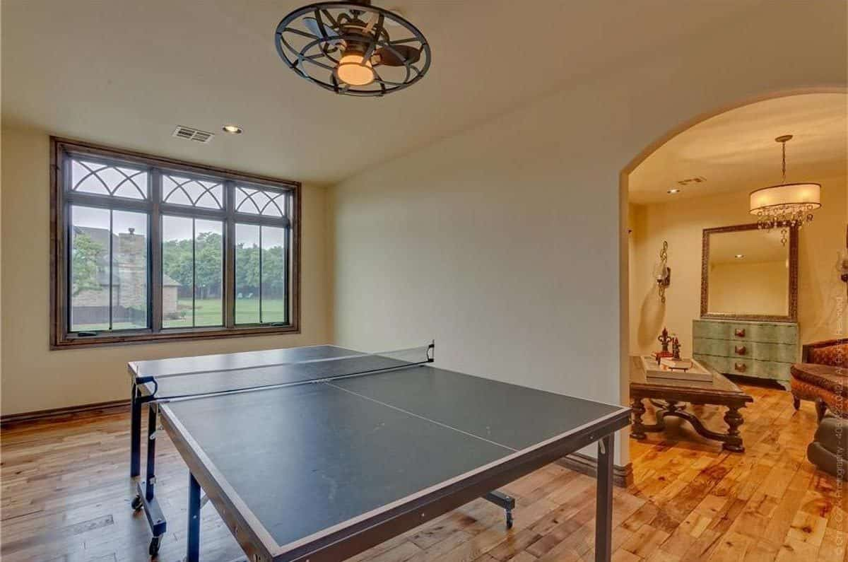 Game room with a pingpong table and an open archway leading to the sitting area.