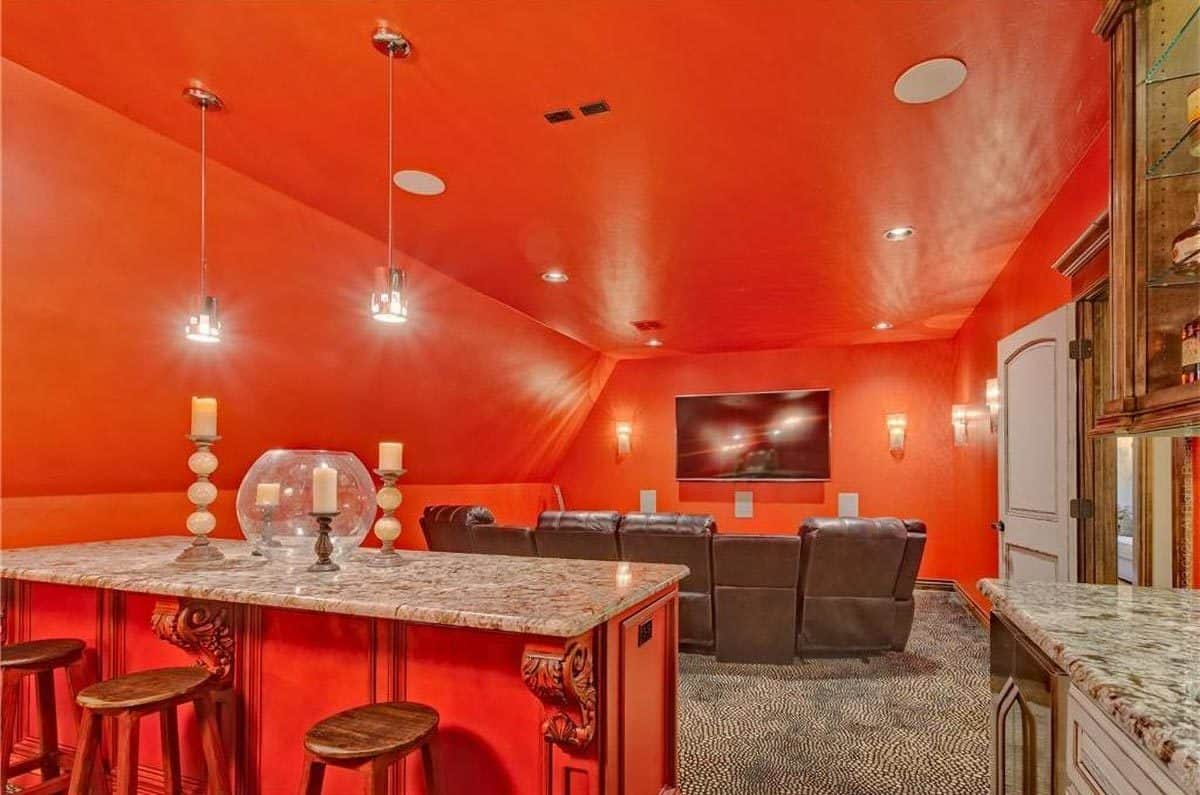 Media room with granite top counters and red vaulted walls matching with the regular ceiling.